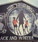 Republican mural, Ardoyne Road, Ardoyne, 2001. Mural draws parallel between the Civil Rights struggle in the USA, specifically the desegregation of schools in Little Rock Arkansas in 1957, and the right of Catholic schoolchildren at to walk to Holy Cross primary school through a Protestant area. Detail: middle panel, 'Everyone has the right to live free from sectarian harassment'; mother taking two Holy Cross children (in red school cardigans) to school, 'It's Black and White', 'Loyalist Bigotry' slogan on wall behind. Photo by Tony Crowley.