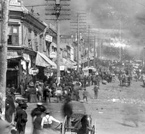 View of Bennett Avenue from Second (2nd) Street during fire of April 25, 1896, Cripple Creek, Colorado; large crowd of men, women and children are gathered on both sides of street's boardwalk; numerous horse- drawn wagons and carriages, many being loaded with personal belongings or commercial goods, are in the street. Photo by Edgar A. Yelton