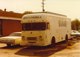 The Fox River Grove (Ill.) Public Library bookmobile in the parking lot of the old library location, from a photograph taken sometime in the 1970's.