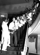 African American musicians stand on a curved staircase in Omaha's Orpheum Theatre playing musical instruments in this 8